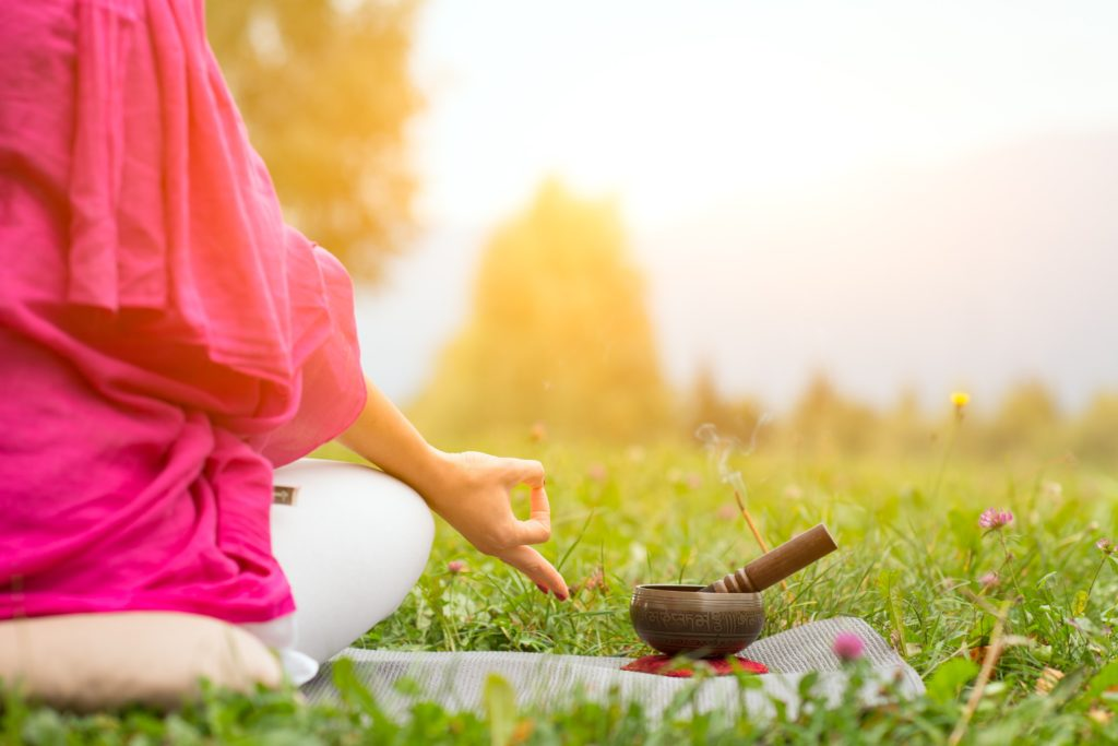 Tibetan bell beside yoga position in a meadow the sun